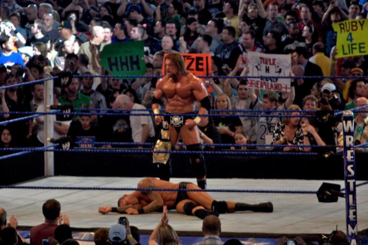 Triple H standing over Randy Orton - Wrestling Examiner